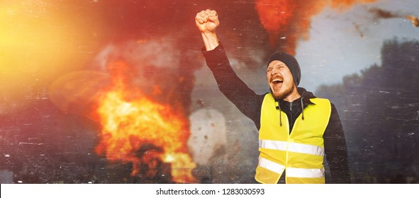 Protests yellow vests. The man raised his hand into a fist and shouted. The concept of revolution and protest, the struggle for equal rights, the electoral movement