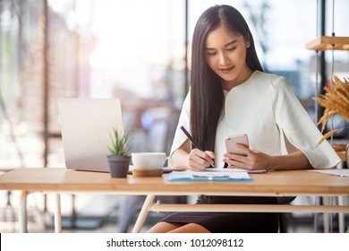 Protrait of Beautiful businesswoman sitting at desk and working with laptop computer.
