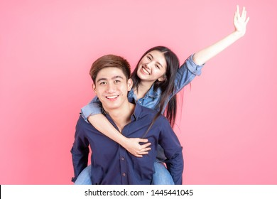 Protrait cheerful young man carrying his girlfriend on back and looking camera with smiley, Teenager couple concept