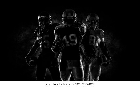 Proud american football players in dark
