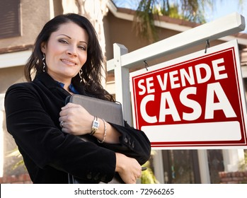 Proud, Attractive Hispanic Female Agent In Front of Spanish Se Vende Casa Real Estate Sign and House.