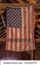 Proud to be an American - tattered American flag hanging from rafters in barn