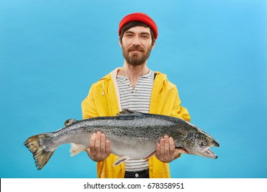 Proud bearded fisherman having glad expression catching big fish having successful day. Handsome male with blue eyes dressed casully came home after going fishing bringing huge trout for supper