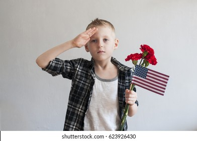Proud  boy celebrating Memorial day with flowers and American flag