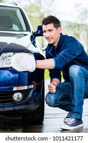 Proud car owner cleaning the headlamps of his luxury sedan with a soft absorbent mitt