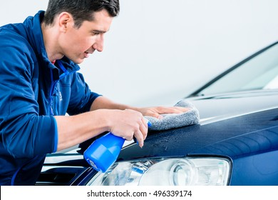 Proud car owner cleaning his vehicle with a sponge and detergent in a spray bottle , close up cropped profile view
