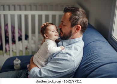 Proud Caucasian father talking to newborn baby girl. Parent holding rocking child daughter in hands. Authentic lifestyle happy parenting fatherhood moment. Single dad family home life.