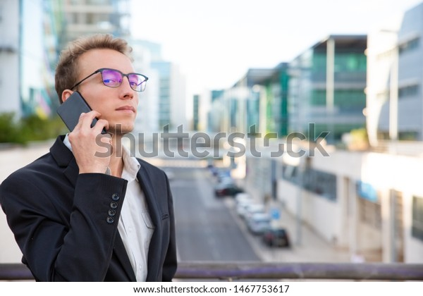 Proud confident businessman calling on cell outside. Young man in office jacket and glasses standing in city street and talking on mobile phone. Phone talk concept