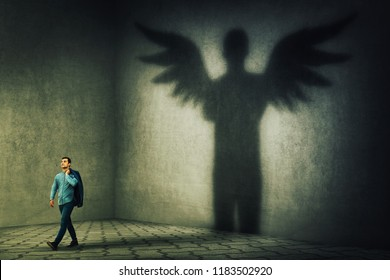 Proud and confident young businessman casting a superhero shadow with angel wings on a dark room wall. Inner power, ambition and leadership concept.