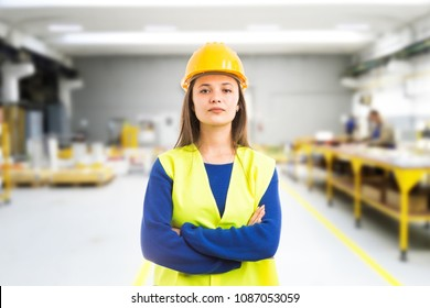 Proud confident young woman engineer with arms crossed as professional supervisor concept on indoor factory background