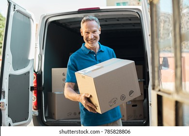 Proud delivery man in blue uniform holding parcel and looking at camera. Smiling mature courier standing in front of cargo van delivering package. Portrait of delivery man holding card box.