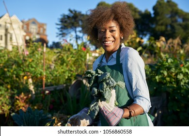 proud diverse millenial posing with freshly picked kale at urban community communal garden