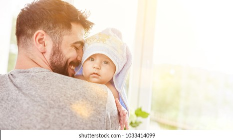 Proud father carries his baby in the towel after bathing