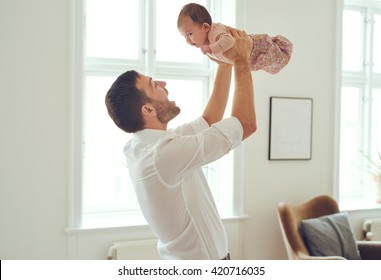 Proud father holding his newborn baby daughter up in the air at home