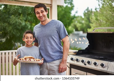 proud father and son showing tray of grilled hot dogs