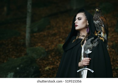 Proud female warrior with hawk .Dark woods background