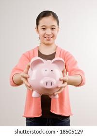 Proud girl holding piggy bank full of savings