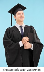 Proud graduate student holding a book on blue background