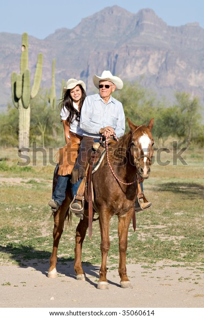 A proud grandfather rides horseback with his beautiful granddaughter.