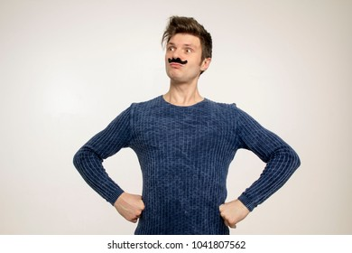 A proud guy with a fake mustache and disheveled hair put his hands on his hips and looks proudly into the distance. Portrait.