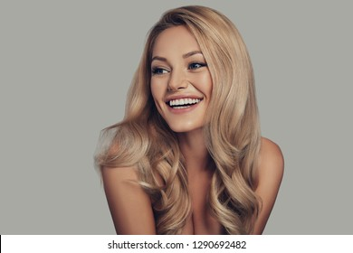 Proud of her perfect hair. Beautiful young woman smiling and looking away while standing against grey background