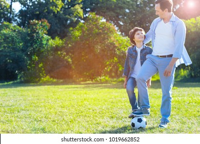 So proud of him. Thoughtful mature man smiling to his son while their legs standing on a soccer ball after an extremely successful training outdoors.