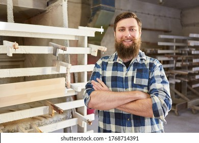 Proud hipster furniture maker in the joinery in front of the wood gluing press