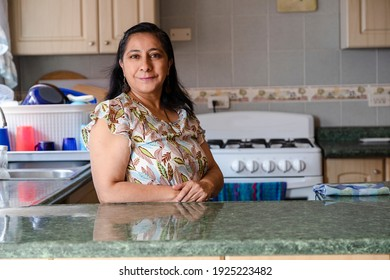 Proud Hispanic woman posing in her kitchen clean-smiling mom standing in the kitchen-woman in the kitchen not cooking