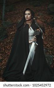 Proud hooded woman with sword and hawk. Forest background