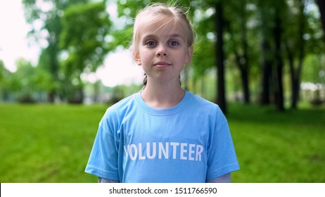 Proud little girl in volunteer t-shirt standing at park, environment protection