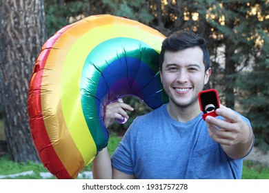 Proud man celebrating diversity with rainbow colored engagement ring