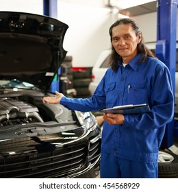Proud mature Vietnamese mechanic showing repaired car