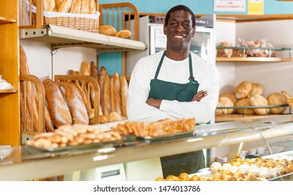 Proud owner of bakery shop standing with arms folded behind counter with fresh baked products