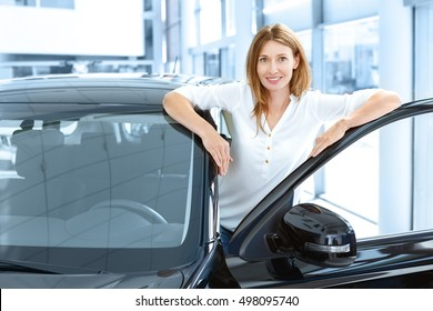Proud owner. Shot of a mature female customer choosing a car at the dealership posing near the vehicle with an open door smiling to the camera happily copyspace