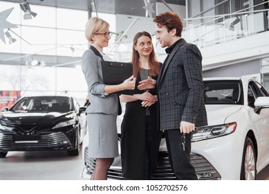 Proud owners. Beautiful young happy couple hugging standing near their newly bought car smiling joyfully showing car keys to the camera copyspace family love relationship lifestyle buying consumerism.