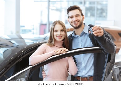 Proud owners. Beautiful young happy couple hugging standing near their newly bought car smiling joyfully showing car keys to the camera copyspace family love relationship lifestyle buying consumerism