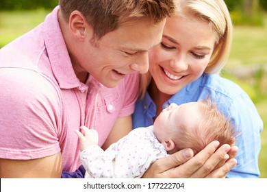 Proud Parents Holding Baby Daughter In Garden