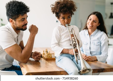 Proud parents watching their child plays trumpet