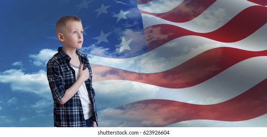 Proud patriotic kid holding his hand on his heart and looks at american flag