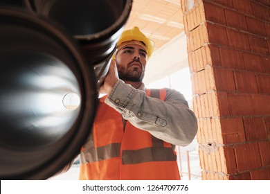 Proud people working in construction site. Portrait of happy white man at work in new house. Professional latino worker carrying pipes and looking away