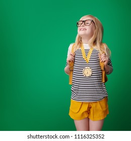proud school girl with backpack with gold medal isolated on green