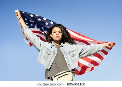 Proud serious young Afro American woman standing on street holding usa flag under blue sky looking at camera. Mixed race lady for democracy, racial equality, fair elections, changes in United States.