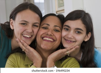 Proud smiling hispanic mother and her two teenage girls at home