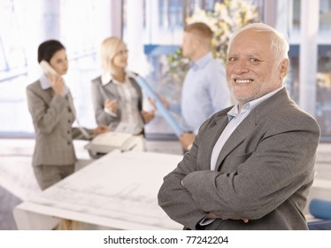 Proud smiling senior businessman standing with arms crossed, smiling, with team working in background.?