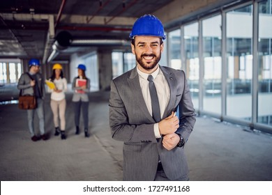 Proud smiling successful bearded architect with helmet on head dressed in suit standing inside of building in construction process and looking at camera. In background are his colleagues.