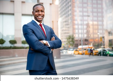 Proud successful businessman executive CEO african american, standing confidently with arms folded in downtown, financial buildings and skyscrapers