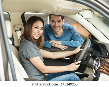 Proud of their new car. Beautiful young couple are examining a new car at the dealership
