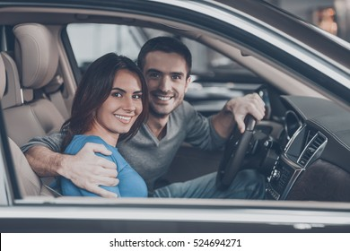 Proud of their new car. Beautiful young couple sitting at the front seat of the car and looking at camera