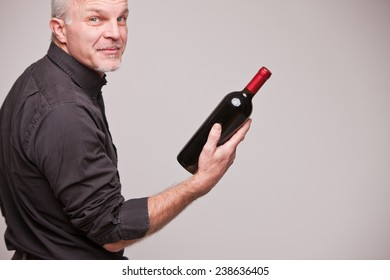 proud wine maker man with a bottle of excellent red wine