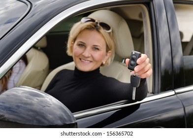 Proud woman driver holding up her car keys out of the open window of the vehicle to show that she has just purchased a new car